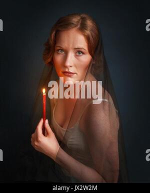 Femme avec une bougie sous voile. Photo d'Halloween. Portrait sombre Banque D'Images