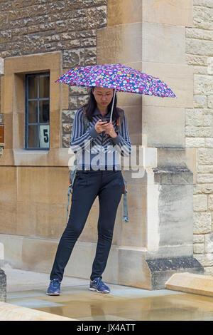 Woman using mobile phone s'abritant sous un parapluie mouillé sur un jour de pluie à Oxford en Août Banque D'Images