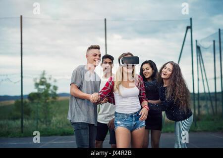 Groupe d'adolescents attrayant à l'extérieur sur une aire de jeux, port de lunettes de réalité virtuelle fille. Banque D'Images