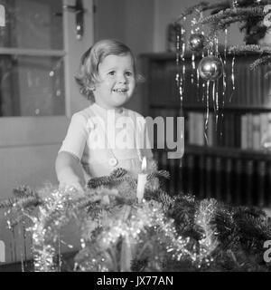 Petite fille, je suis debout près de l'arbre de Noël. Banque D'Images
