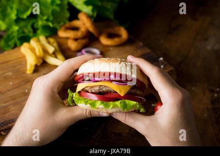 Cheeseburger. Man hands holding burger avec fromage, oignons rouges, tomates, laitue salade verte et des cornichons. Banque D'Images