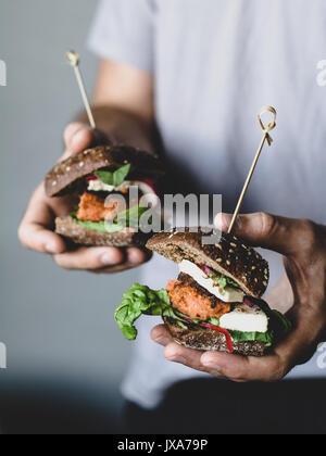 Les jeunes carottes végétarienne holding hipster Burgers au tofu. Vue rapprochée, selective focus Banque D'Images