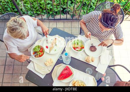 Maman moderne et jeune fille au dîner assis à la table dans un parc aquatique sur l'été. Concept de belles personnes Banque D'Images