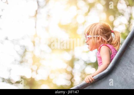 Image en gros plan avec une petite fille s'amusant sur une diapositive à partir d'une aire de jeux, sur une journée Banque D'Images