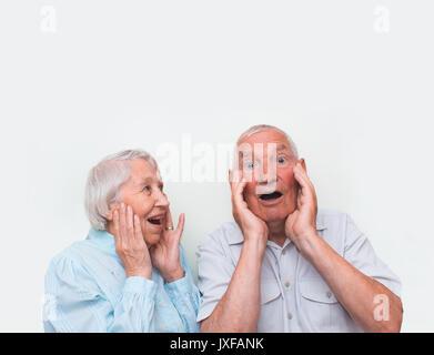 Le vieux couple surpris en soulevant les deux mains Banque D'Images