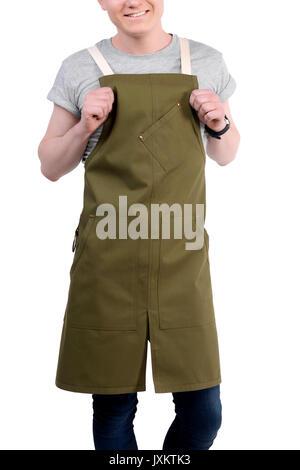 Jeune cuisinier ou serveur posant, porter un tablier et des t-shirt gris isolé sur fond blanc. Café café barista uniforme.