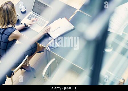 Angle de vue haute fenêtre young businesswoman typing on laptop at office desk