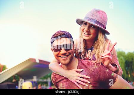 Portrait de jeune femme couverte de poudre de craie de couleur de petit ami au festival piggyback