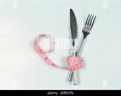 Fourchette et couteau enroulé à l'intérieur de ruban rose Banque D'Images