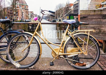 Vélo d'or garde-corps appuyé contre plus d'un canal à Amsterdam