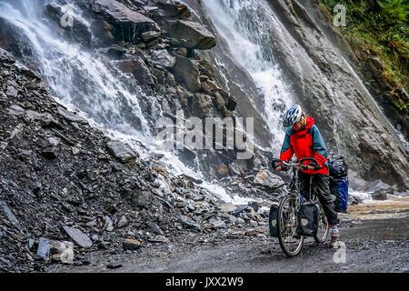 Femme passant l'une des nombreuses cascades tout en vélo à travers la gorge du tigre bondissant, province du Yunnan, Banque D'Images