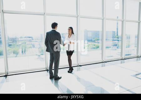 Vue de dessous de deux jeunes hommes d'affaires sont debout dans un bureau moderne, doté de fenêtres panoramiques. Banque D'Images