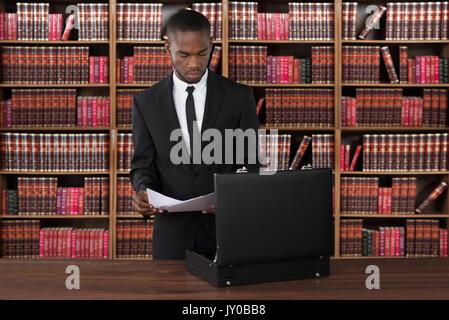 Avocat avec Papiers et Briefcase At Desk In Office