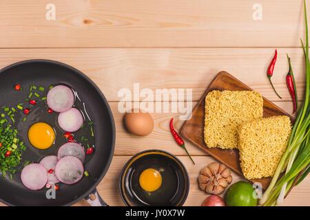 Des nouilles instantanées pour cuisiner et manger dans le plat avec les oeufs et les légumes sur fond de bois. Banque D'Images