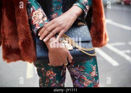 a9a1dcd3ee03 Femme en costume de soie noir avec sac à main, Close up mid section Banque