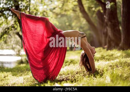 Fit young Beautiful woman jupe rouge de l'extérieur dans le parc de l'été dernier, faisant du yoga pose du pont Banque D'Images