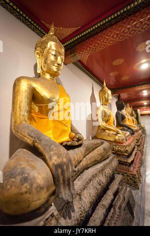 Rangée de bouddhas assis d'or priant au Wat Pho (Temple du Bouddha couché), Bangkok, Thaïlande Banque D'Images