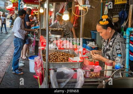 Vendeurs de rue vendant châtaignes d'or chaud dans les marchés de Chinatown, Bangkok, Thaïlande