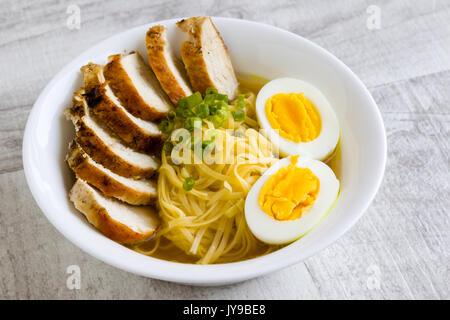 Soupe ramen japonais avec du poulet et un œuf dans un bol blanc Banque D'Images