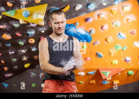 Rock climber mettant la craie sur les mains dans la salle d'escalade intérieur Banque D'Images