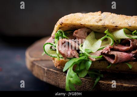 Sandwich de pain de blé entier avec du rosbif, concombre et roquette Banque D'Images