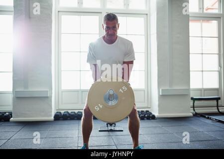 Portrait of a young man in sportswear seul se tenant dans une salle de sport axés sur la levée de poids lors d'un Banque D'Images