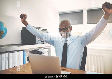 Smiling African businessman célèbre avec ses bras levés en l'air tandis qu'assis à un bureau dans son bureau à domicile Banque D'Images