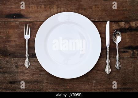 Place d'un ensemble salle à manger d'une plaque vide avec une cuillère, fourchette et couteau sur un vieux fond Banque D'Images