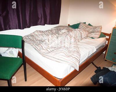 Unmade étudiant malpropre grand lit chambre président et les vêtements; Angleterre; UK Banque D'Images
