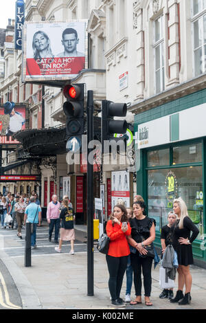 Un groupe de femmes touristes attendant de traverser la route à l'extérieur de l'Apollo Theatre Shaftesbury Ave, Soho, Londres W1D 7EZ, Royaume-Uni