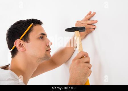 Vue latérale du jeune homme hammering nail sur mur blanc à la maison