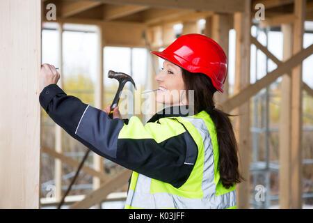 Female Carpenter Hammering Nail dans le bois sur le site Banque D'Images