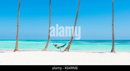 Juanillo Beach (playa Juanillo), Punta Cana, République dominicaine. Femme de vous détendre sur un hamac sur une Banque D'Images