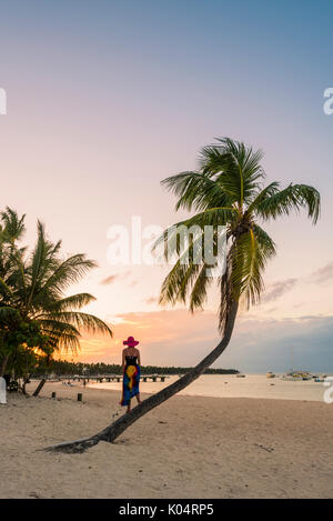 La plage de Cabeza de Toro, Punta Cana, République dominicaine. Femme debout sur le tronc d'un palmier (MR). Banque D'Images
