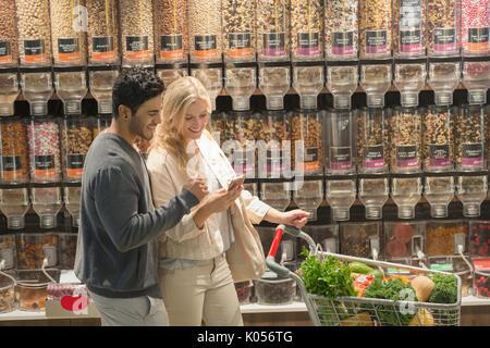 Jeune couple using cell phone, marché des épiceries. Banque D'Images