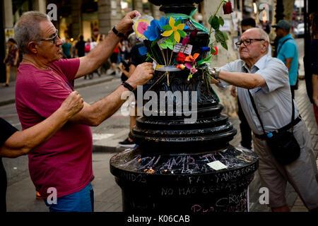 Barcelone, Espagne. Août 21, 2017. Deux hommes place fleurs à un lampadaire de Las Ramblas de Barcelone, en mémoire de l'attaque terroriste aux victimes le même jour que Younes Abouyaaqoub, identifiés comme chauffeur de van qui a accéléré le long de la rue Las Ramblas le jeudi, a été abattu par des agents de police catalane dans le village de Subirats. Crédit: Jordi Boixareu/Alamy Live News
