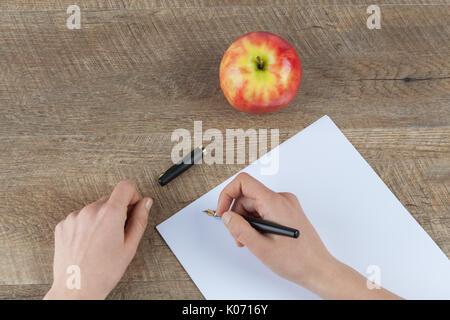 Femme hands holding stylo et feuille de papier libre sur table en bois avec pomme rouge Banque D'Images
