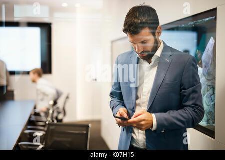 Beau jeune homme d'affaires en costume bleu holding mobile phone Banque D'Images