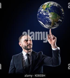Businessman tient le monde avec un doigt. Monde fournie par la NASA Banque D'Images