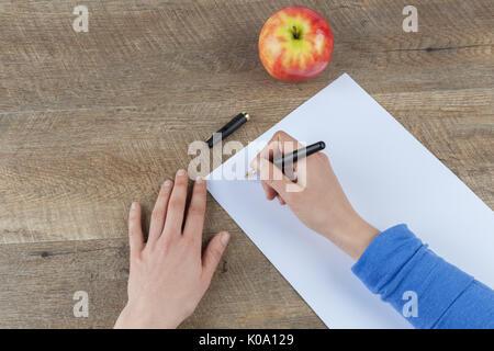 Femme hands holding stylo et feuille de papier blanc sur la table en bois avec pomme rouge Banque D'Images