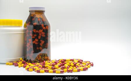 Capsule rouge, jaune et des bouteilles de pilules antibiotiques, résistance aux médicaments sur fond blanc avec Banque D'Images