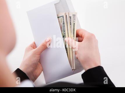 Portrait of businesswoman putting-américain dans les billets au bureau de l'enveloppe Banque D'Images