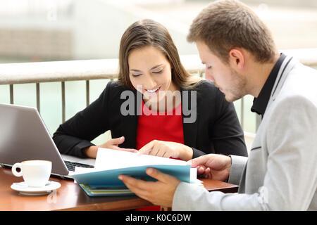 Deux documents de consultation des dirigeants heureux de travailler ensemble dans un café Banque D'Images