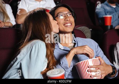 Image de jeune couple aimant assis dans le cinéma voir le film et en l'embrassant Banque D'Images