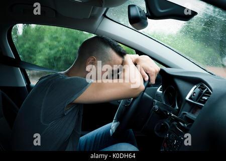 Closeup of a young caucasian man sitting at le siège conducteur d'une voiture avec sa tête reposant sur le volant, Banque D'Images