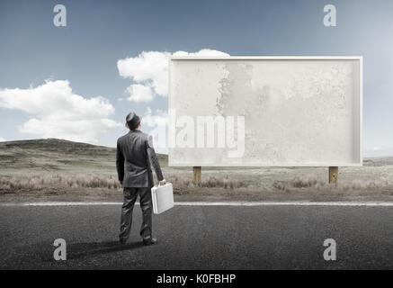 Un homme d'affaires et commandes devant un panneau d'affichage vierge. Banque D'Images