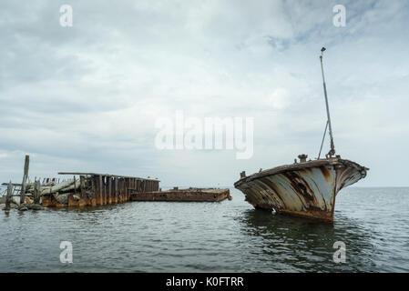 Vieux bateau épave sur la côte, mer bleue et voilier sur l'arrière-plan. harilaid, petite île de l'Estonie, de l'Europe. Banque D'Images