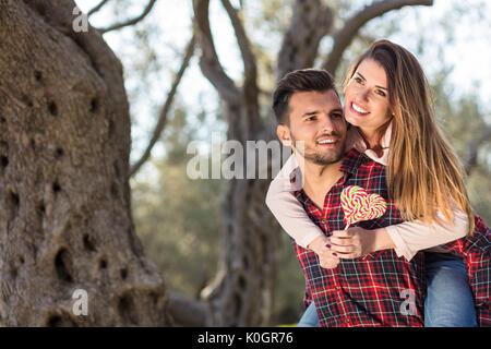 Portrait of smiling handsome man giving piggy back pour sa petite amie dans la nature Banque D'Images