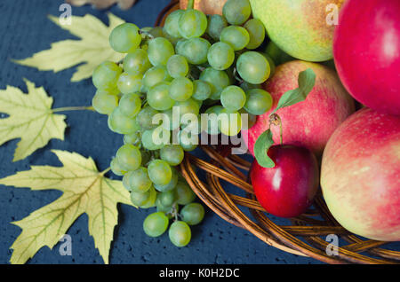 Récolte de fruits mûrs - pommes, raisins, prunes, les poires dans une grande plaque de bois sur un fond noir, décoré Banque D'Images