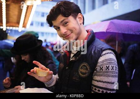 Jeune homme avec une pâtisserie dans un marché de Noël Banque D'Images